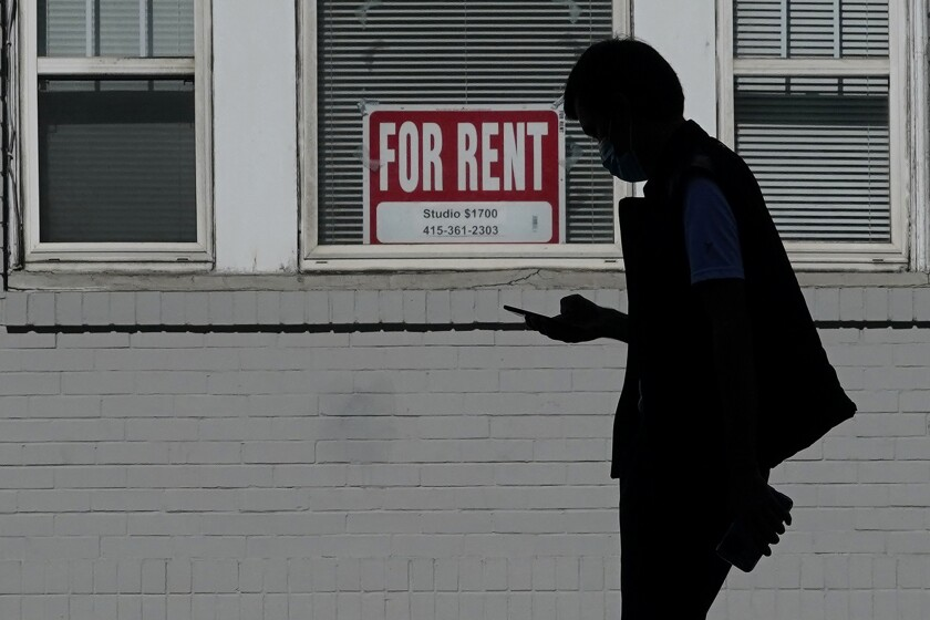 FILE - In this Oct. 20, 2020 file photo, a man walks in front of a For Rent sign in a window of a residential property in San Francisco. California has been slow to distribute rental assistance money for residents struggling during the coronavirus pandemic, and the state risks forfeiting hundreds of millions of dollars in federal funds, auditors said Thursday, Sept. 16, 2021. (AP Photo/Jeff Chiu, File)