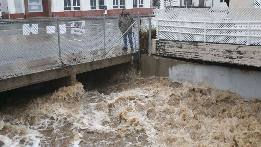 Rain water pours down a storm drain on Beach St. in downtown Laguna Beach, from Laguna Canyon, after
