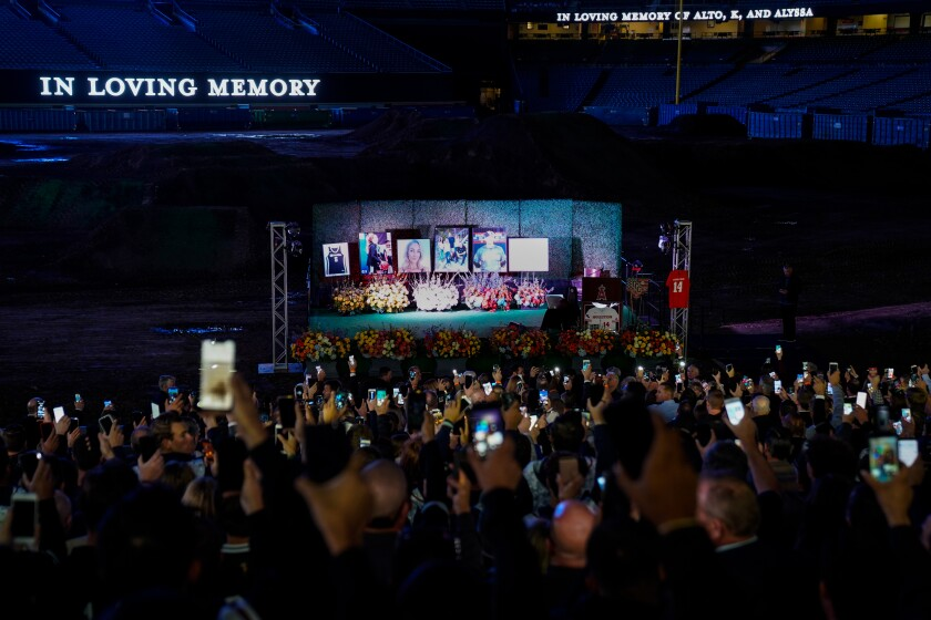 People hold up cell phones with lights on, during a celebration of life ceremony at Angel Stadium on Monday to honor the lives of John, Keri and Alyssa Altobelli, who were among the nine killed in a helicopter crash that also claimed the lives of Lakers legend Kobe Bryant and his daughter Gianna.
