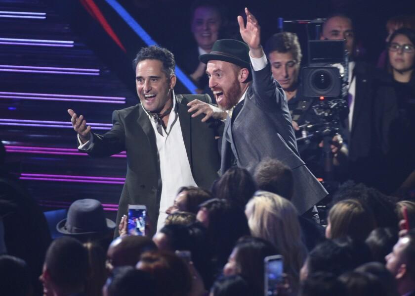 Jorge Drexler, izq., y Jesús Martos reaccionan entre la audiencia cuando el primero es anunciado como ganador del premio al Álbum del Año en el Latin Grammy.