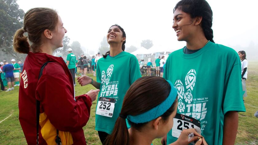 Twins Priyanka, center, and Gitanjali Multani, right, share a laugh as their walker numbers are applied at the Ovarian Cancer Alliance's Teal Steps fundraiser on Sunday in Coronado.