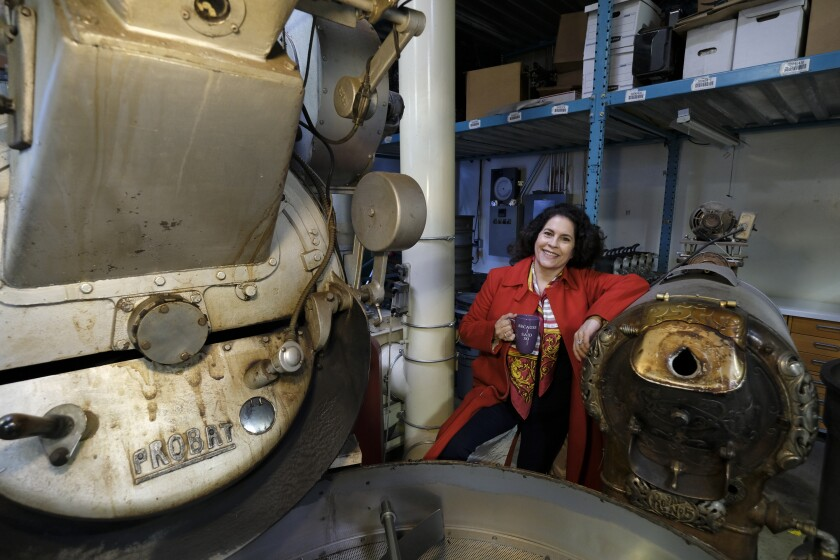 In this photo taken Wednesday, March 11, 2020, Renee Brown, vice-president of Wild Card Roasters, poses between a pair of coffee roasters at her roastery and cafe in San Rafael, Calif. As the coronavirus spreads, many small business owners are rethinking their strategies and adjusting the way they work. (AP Photo/Eric Risberg)