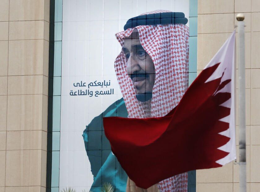 """A Qatari flag flies in front of a banner showing Saudi King Salman with Arabic reads, """"We pledge you to listen and obey"""" at a trade center in Riyadh, Saudi Arabia, Monday, Dec. 9, 2019 ahead of the Gulf Cooperation Council """"GCC"""", 40th summit. (AP Photo/Amr Nabil)"""