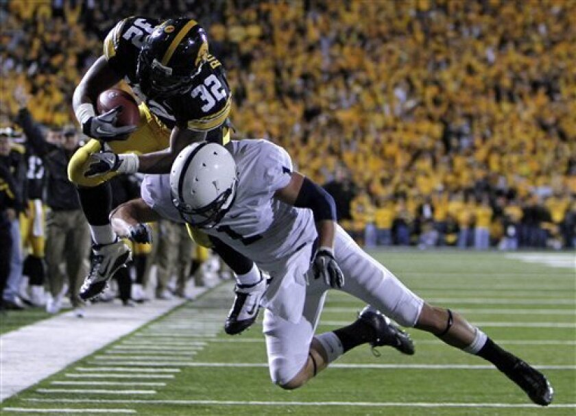 Iowa running back Adam Robinson, left, leaps over Penn State safety Nick Sukay during the first half of an NCAA college football game, Saturday, Oct. 2, 2010, in Iowa City, Iowa. (AP Photo/Charlie Neibergall)