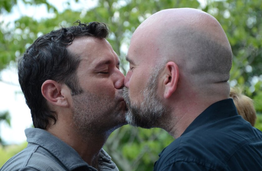 Duane Smith, left, and Knol Aust of Jackson, Miss., kiss in front of the Hinds County courthouse in Jackson during their marriage ceremony on Monday.