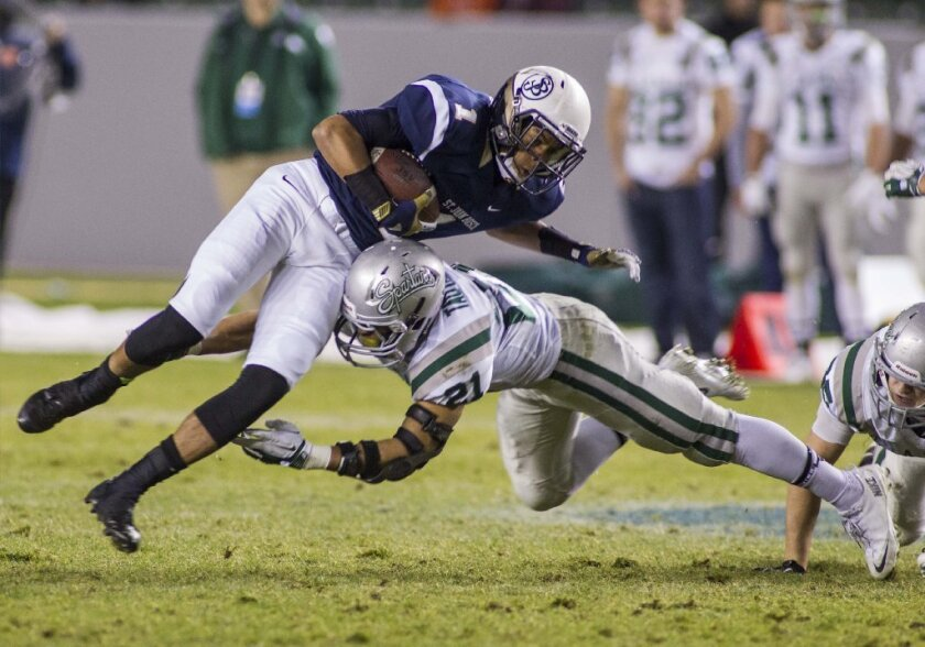 St. John Bosco's Shay Fields jumps over De La Salle's Dasmond Tautalatasi in the first half of a CIF Open Division high school football championship game in Carson on Dec. 21. Football is among the sports that put teen athletes at risk for head injury.