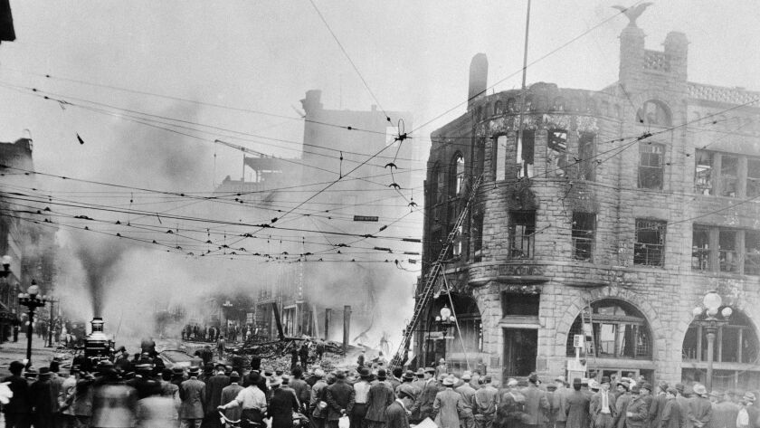 A crowd gathers to look at the remains of The Times building in downtown Los Angeles after the 1910