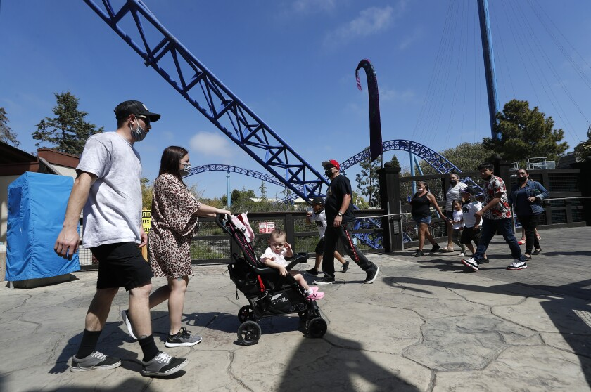 Two adults with a child in a stroller walk near a roller coaster
