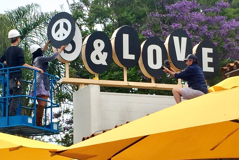 "A temporary sign, ""peace and love,"" was affixed over the Sambo's restaurant sign."
