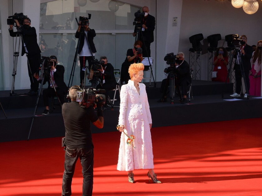 Actress Tilda Swinton holds a fanciful golden mask on the red carpet at the 77th Venice Film Festival.
