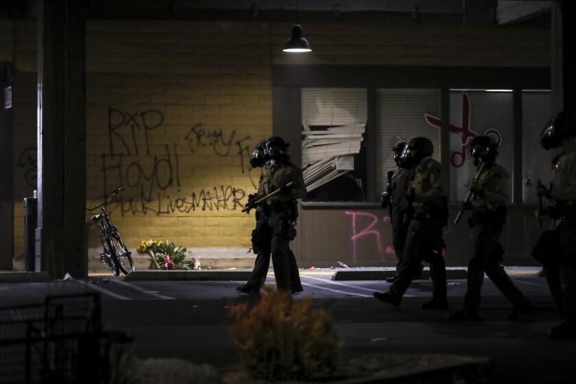Deputies and La Mesa police walk in the La Mesa Springs Shopping Center