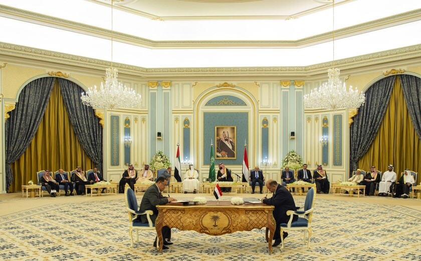 In this photo released by the Saudi Royal Palace, Yemeni Southern Transitional Council member and former Aden Governor Nasser al-Khabji, left, and Yemen's deputy Prime Minister Salem al-Khanbashi sign a power-sharing deal in Riyadh, Saudi Arabia, Tuesday, Nov. 5, 2019. Yemen's internationally recognized government signed a power-sharing deal with Yemeni separatists that are backed by the United Arab Emirates. A picture of Saudi Arabia's founder late King Abdul Aziz Al Saud hangs on wall. (Bandar Aljaloud/Saudi Royal Palace via AP)