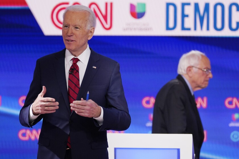 Sen. Bernie Sanders, I-Vt., right, and former Vice President Joe Biden, left, return to the stage after a commercial break in a Democratic presidential primary debate at CNN Studios, Sunday, March 15, 2020, in Washington. (AP Photo/Evan Vucci)