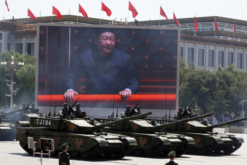 In 2015 Chinese President Xi Jinping is displayed on a screen as Chinese battle tanks take part in a parade in Beijing.