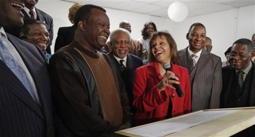 In this Feb. 7, 2013 photo, from left Gail Mahome, Dr. Willie Wilson and Dr. John Gray, smile at a news conference in Chicago, as they join other members of the International Ministers & Community Alliance in endorsing Robin Kelly, center, a former Illinois state representative and Democratic hopef