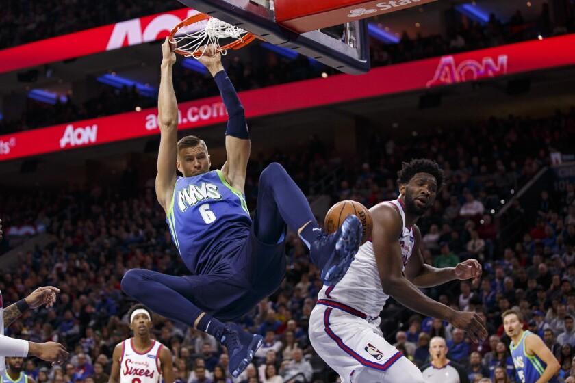 Mavericks forward Kristaps Porzingis dunks against 76ers center Joel Embiid during the first half Dec. 20 in Philadelphia.
