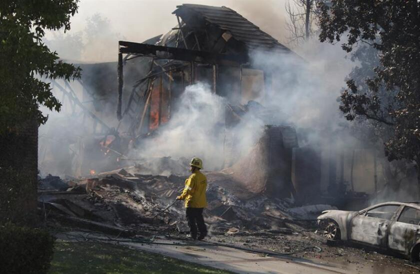 A firefighter surveys the smoldering ruins of a home destroyed by the Woolsey Fire in Agoura, California, Nov. 9, 2018. EPA-EFE/Mike Nelson