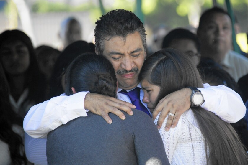 Andres Gonzalez is hugged by friends of his daughter Andrea at Fairhaven Memorial Park and Mortuary in Santa Ana on Saturday. Andrea, 13, was killed by a hit-and-run driver on Halloween.