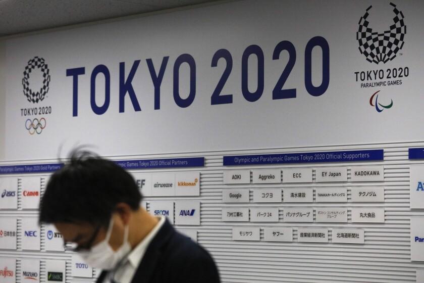 Un periodista aguarda por el inicio de una rueda de prensa del comité organizadores de los Juegos Olímpicos de Tokio 2020, el martes 24 de marzo de 2020. El COI anunció el aplazamiento de los Juegos a 2021 debido a la pandemia del coronavirus. (AP Foto/Jae C. Hong)