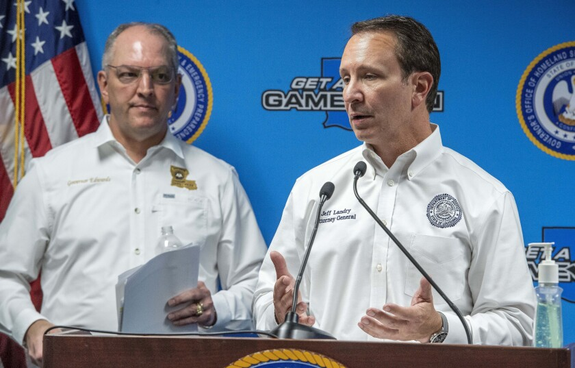 FILE- In this April 6, 2020 file photo, Attorney General Jeff Landry, right, speaks about medicines being donated by drug companies to help the fight against the coronavirus during a press conference in Baton Rouge, La. Louisiana Gov. John Bel Edwards listens at left. Landry is quarantining himself after testing positive for the coronavirus. His spokesman said Tuesday, July 14 that the prominent Republican elected official has no symptoms of COVID-19 (Bill Feig/The Advocate via AP, Pool, File)