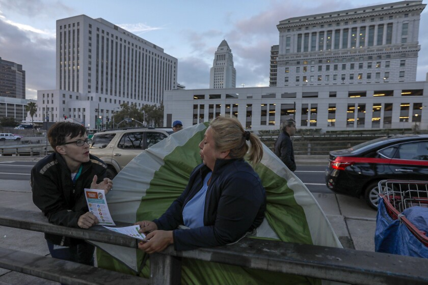 Amy Perkins of the Los Angeles Homeless Services Authority, left, explains new rules and restrictions to Leticia Cervantes, who lives in a tent.