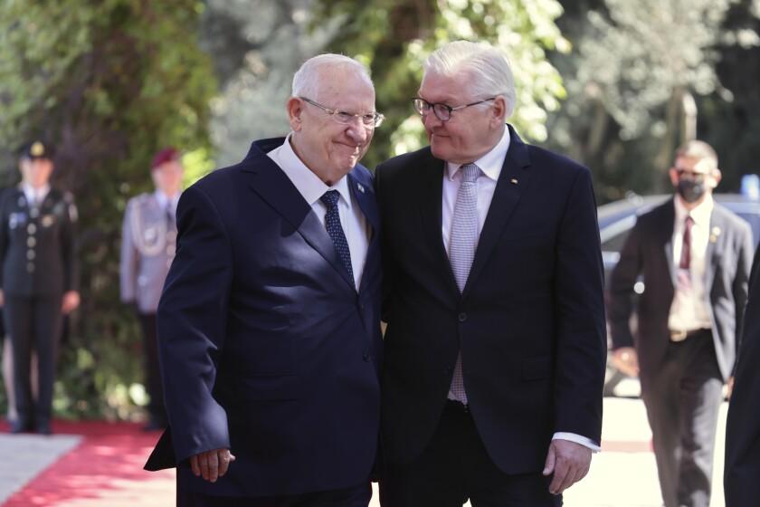 Israeli President Reuven Rivlin, left, walks with German President Frank-Walter Steinmeier at the president's residence in Jerusalem, Thursday, July 1, 2021. (AP Photo/Tsafrir Avayov)