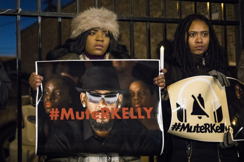 FILE - #MuteRKelly supporters protest outside R. Kelly's studio, Wednesday, Jan. 9, 2019, in Chicago. Accusers and others demanding accountability for the R&B superstar over allegations that he was abusing young women and girls for decades say it took so long to get to a guilty verdict in part because his targets were Black. Kelly was convicted Monday, Sept. 27, 2021, in his sex trafficking trial. Those who work against sexual violence say Black women and girls who want to speak out face a society that hypersexualizes them from a young age. (Ashlee Rezin/Chicago Sun-Times via AP, File)