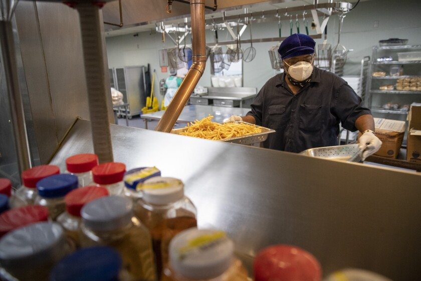 Chef O.J. Hutson cooks French fries in a fryer as he prepares for lunch at the Union Rescue Mission.