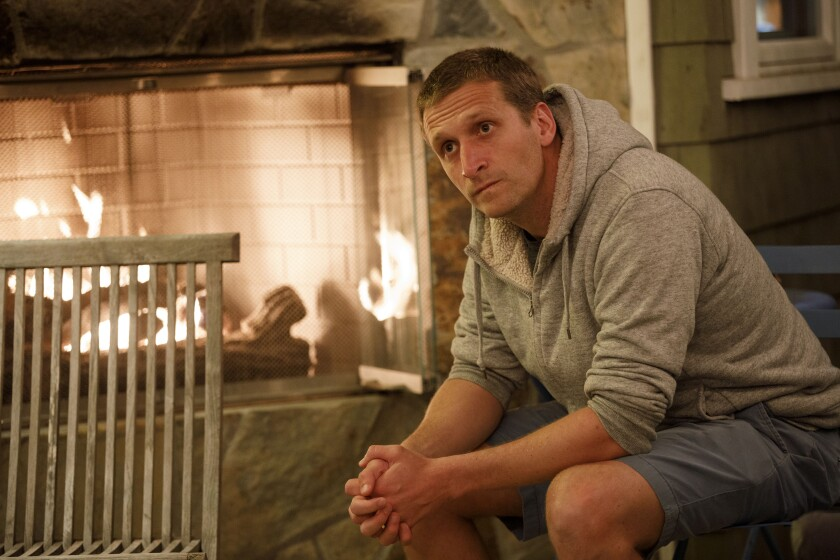 Andrew Herzik by the fireplace in his backyard.