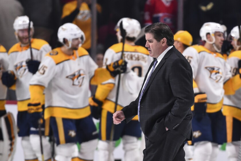 Predators coach Peter Laviolette walks past his team as they celebrate a victory over the Canadiens on Feb. 10, 2018.