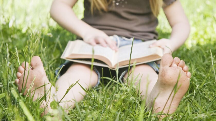 Girl lying on meadow reading a book
