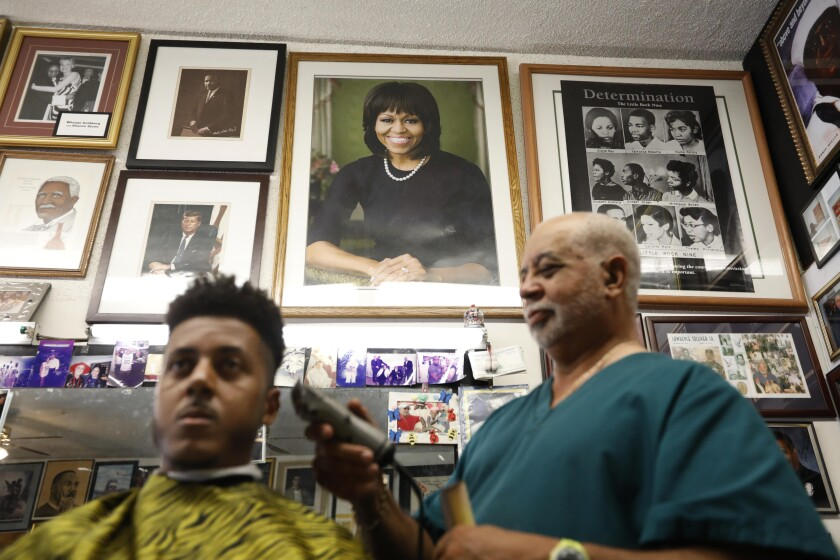 Lawrence Tolliver cuts the hair of Arthur Gomez