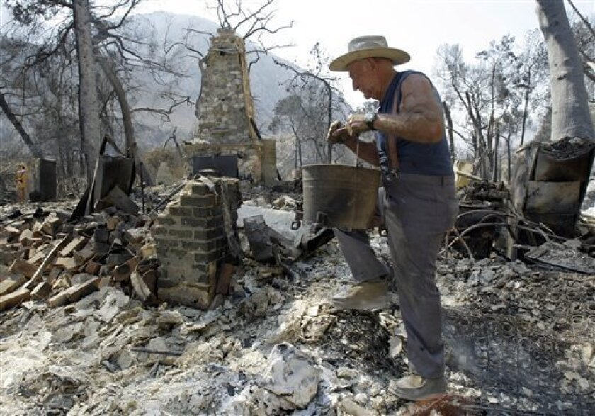 FILE - In this file photo taken Sept. 4, 2009, Lew Johnson, 74, carries a bucket of recovered items as he returns for the first time to the ruins of his home on Stonyvale Road in Big Tujunga Canyon in the Angeles National Forest, in Los Angeles. Months before a wildfire blackened 250 square miles a