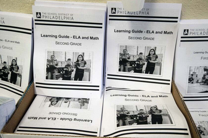 In this Wednesday, March 25, 2019, photo are learning guides to be distributed to students at John H. Webster Elementary School in Philadelphia. Only about half of the district's high school students have a laptop or tablet and home internet service. As schools now appear likely to be closed due to the coronavirus for longer than anticipated, the district plans to buy 50,000 Chromebooks and begin online instruction by mid-April. (AP Photo/Matt Rourke)