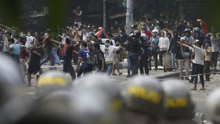 Supporters of the losing presidential candidate clash with police Wednesday, May 22, 2019, in Jakart