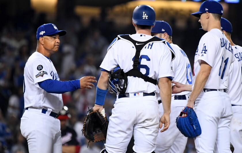 Dodgers manager Dave Roberts pulls pitcher Walker Buehler, right, out of the game in Game 5 of the NLDS at Dodger Stadium on Oct. 9.