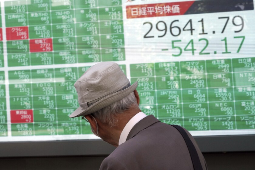 A man wearing a protective mask looks at an electronic stock board showing Japan's Nikkei 225 index at a securities firm Wednesday, Sept. 29, 2021, in Tokyo. Asian shares fell sharply on Wednesday after a broad slide on Wall Street as investors reacted to a surge in U.S. government bond yields. (AP Photo/Eugene Hoshiko)