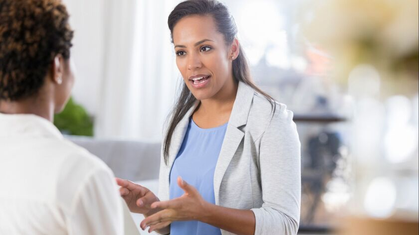Businesswoman uses laptop while meeting with client