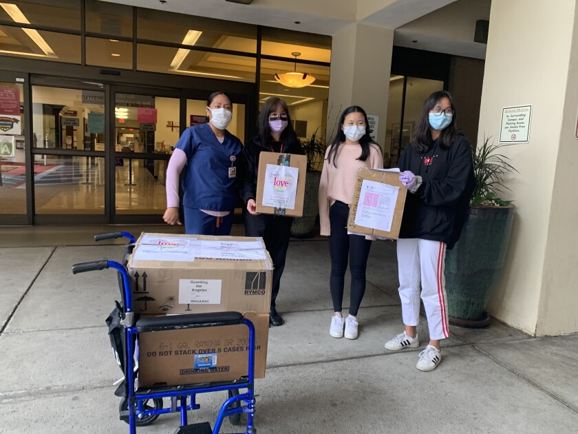 Ruby Gao, right and Katherine Ge, second to right, donated surgical masks to Alvarado Hospital through their Project Butterfly.
