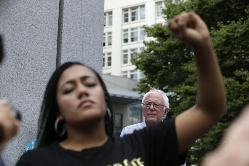 Protester and Bernie Sanders