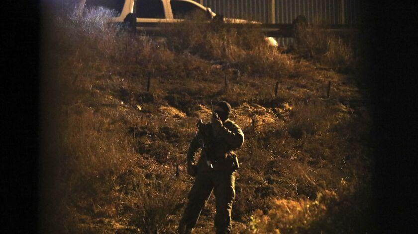 A U.S. Border Patrol agent keeps an eye on a group of Honduran migrants standing near the border wal