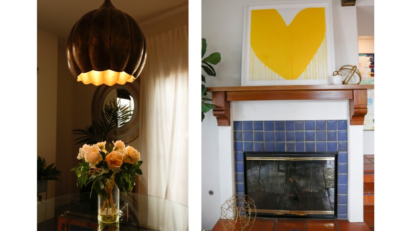 A gold, tulip-shaped pendant light, left, hangs above the glass dining table. A large yellow heart h
