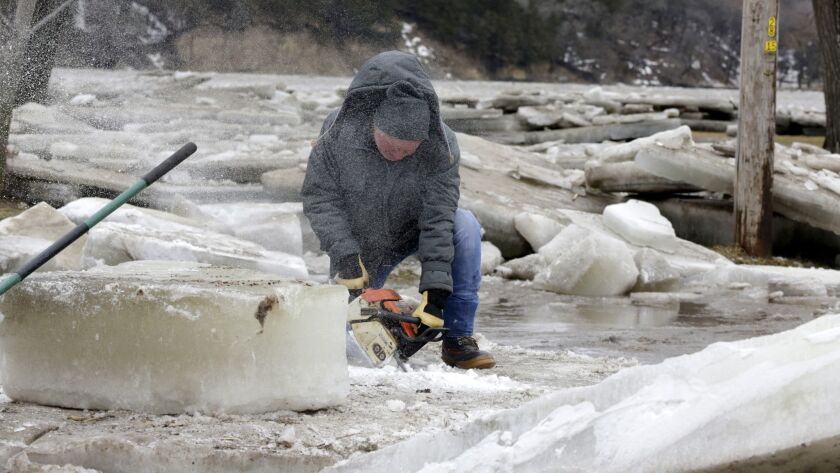 Jim Freeman tries to saw through thick ice slabs on his property in Fremont, Neb., after the ice-covered Platte River flooded its banks.