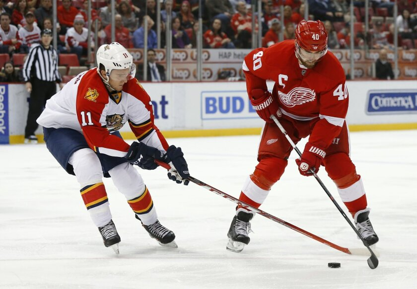 Florida Panthers center Jonathan Huberdeau (11) defends Detroit Red Wings left wing Henrik Zetterberg (40) in the second period of an NHL hockey game, Monday, Feb. 8, 2016 in Detroit. (AP Photo/Paul Sancya)