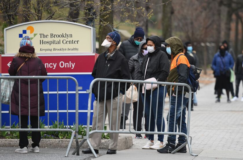 People who believe they have COVID-19, and who meet the criteria, wait in line to be pre-screened for the coronavirus outside of the Brooklyn Hospital Center on March 20, 2020 in the Brooklyn borough of New York.