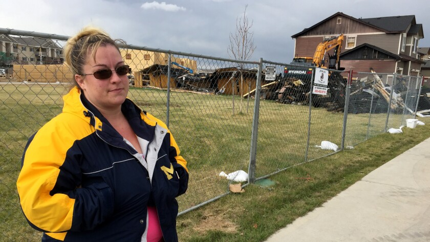 Heather Sawlidi, 31, stands in front of the remains of a home that exploded April 17 in Firestone. S