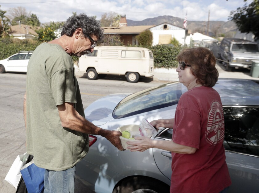 Monica Ciafardini, who sees George Contreras daily on her dog walk by Walt Disney Elementary School where Contreras is a crossing guard, gives him some dog supplies for his surviving dog Scout. His other dog, Blackie, died on Feb. 13 in a fire that tore through his home.