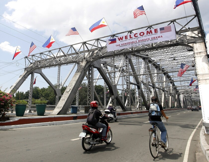 A banner and flags adorn a bridge in Manila as the Philippines prepare for a visit by President Obama.