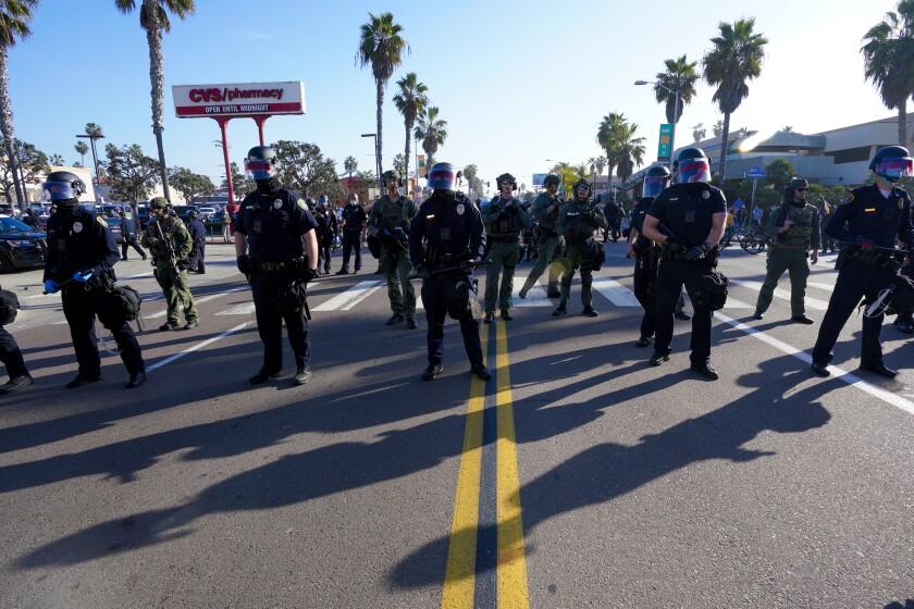 La policía de San Diego toma posiciones en Mission Boulevard en Pacific Beach el sábado.