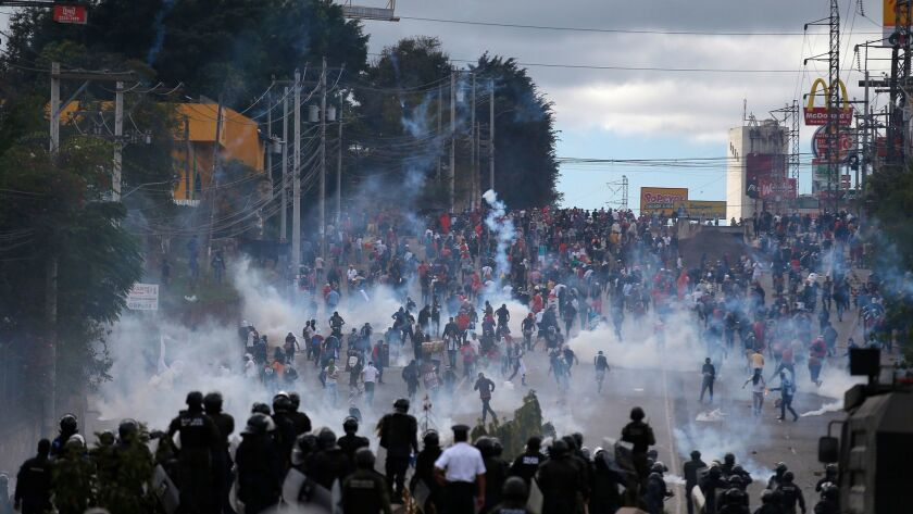 Soldiers and police launch tear gas at demonstrators marching to the national stadium to protest the